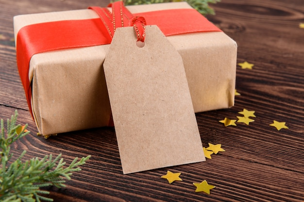 Christmas gift tag mock up with gift box wrapped in craft recycled paper with red ribbon