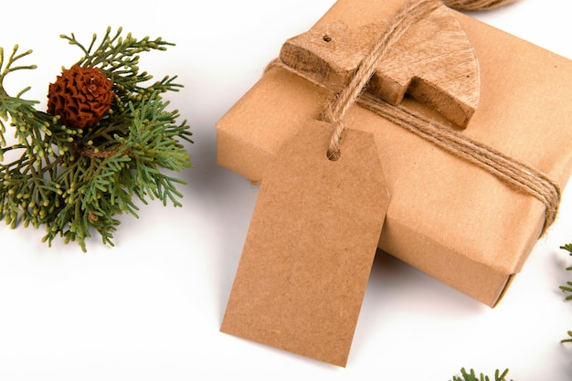 Christmas gift tag mock up with gift box wrapped in craft recycled paper with rope