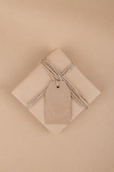 크리스마스 선물 태그는 공예 종이 배경에 밧줄로 공예 재활용 종이에 싸서 선물 상자를 모의합니다.