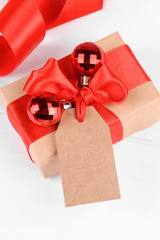 Christmas gift tag with gift box wrapped in craft recycled paper with red ribbon bow on a white background.