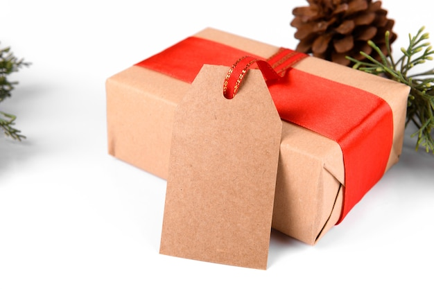 Christmas gift tag with gift box wrapped in craft recycled paper with red ribbon and pine cones on a white background.