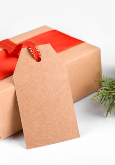 Christmas gift tag with gift box wrapped in craft recycled paper with red ribbon on a white background.