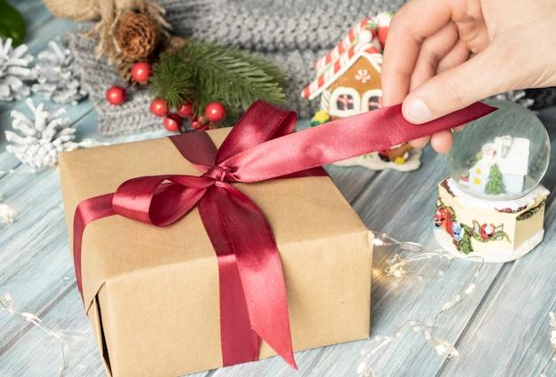 クリスマスプレゼント。伝統的な装飾が施されたギフトボックスを保持している女性の上面図。モミの枝、モミの円錐形、およびベリーと木製のテーブル