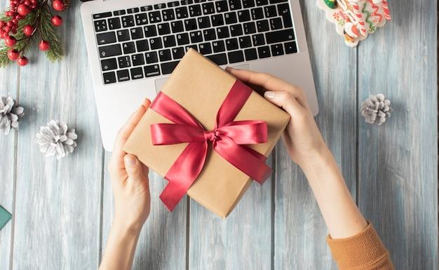 伝統的な装飾のギフトボックスを保持している女性のクリスマスプレゼントの上面図