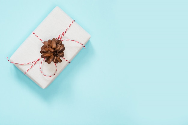 Christmas gift in white paper with cone on blue background