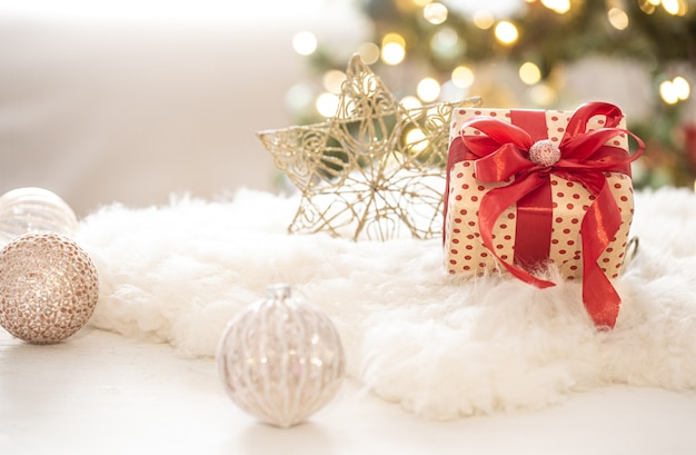 Christmas gift with decorations on the tree on a light blurred bokeh background copy space.
