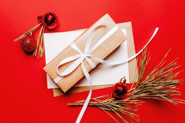 Рождественский подарок с еловой веткой и игрушкой на красном