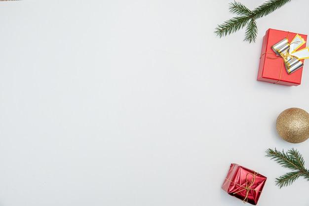 白い背景で隔離の金と赤のボールの弓とクリスマスプレゼント