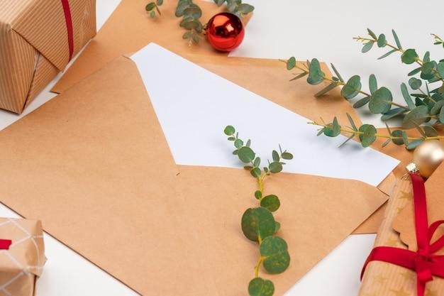 Рождественский подарок с красным бантом и поздравительной открыткой на белом деревянном фоне