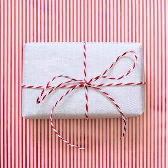 Christmas gift with red ribbon on stripes surface.