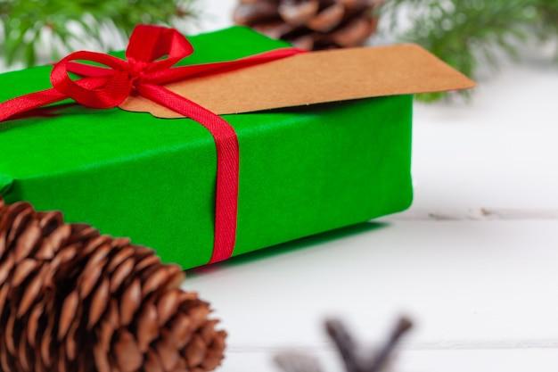 나무 배경에 가문비나무 가지가 있는 크리스마스 선물