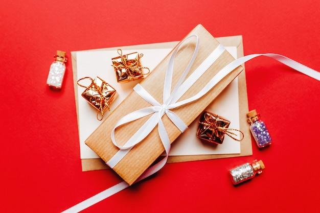 Рождественский подарок с игрушкой на красном новогоднем фоне концепции