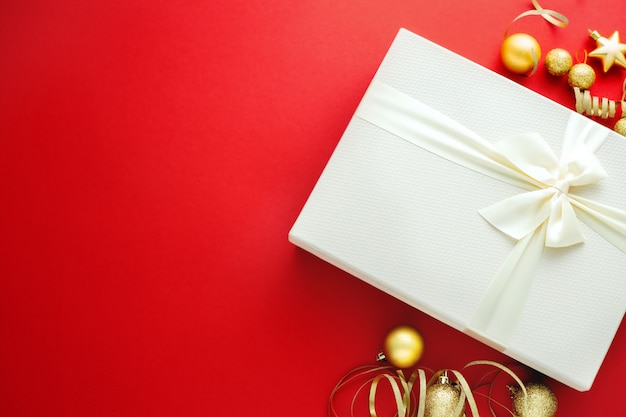 Christmas gift with white bow on red background