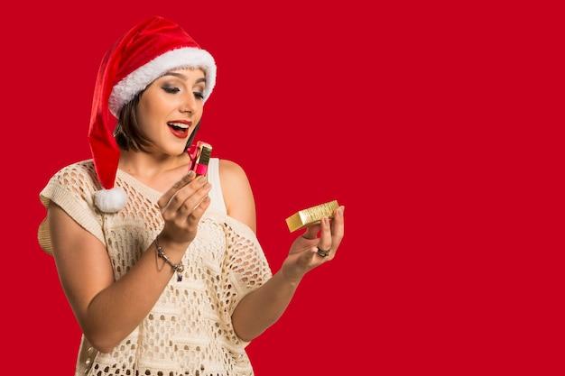 クリスマスギフト-サンタの帽子をかぶった若い美しい笑顔の女性、驚きと幸せのギフトを開く女性。赤い背景の上のブルネットの女性の面白いかわいい写真