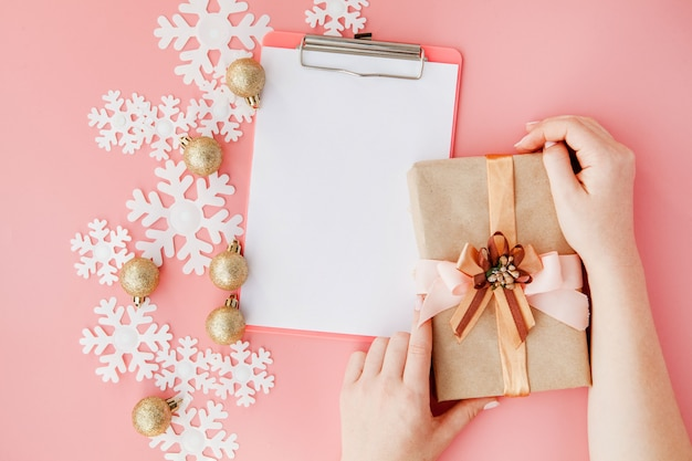 Christmas gift in women's hands and notebook on a pink , a view from above