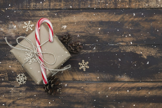 .christmas gift wrapped in craft paper with candy cane on brown wooden table.