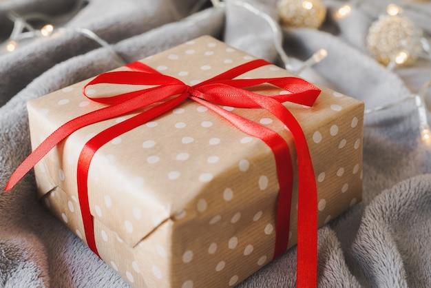 Рождественский подарок в крафтовой бумаге в горошек с красной лентой