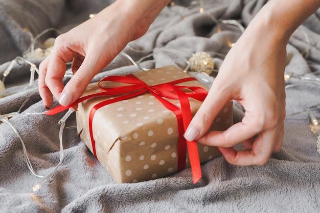Рождественский подарок, завернутый в бумагу в горошек с красной лентой, женские руки держат ленты