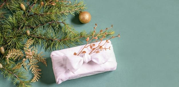日本の伝統的な風呂敷スタイルを包むクリスマスプレゼント。クリスマス休暇のためのプラスチックの無料手作りギフト。