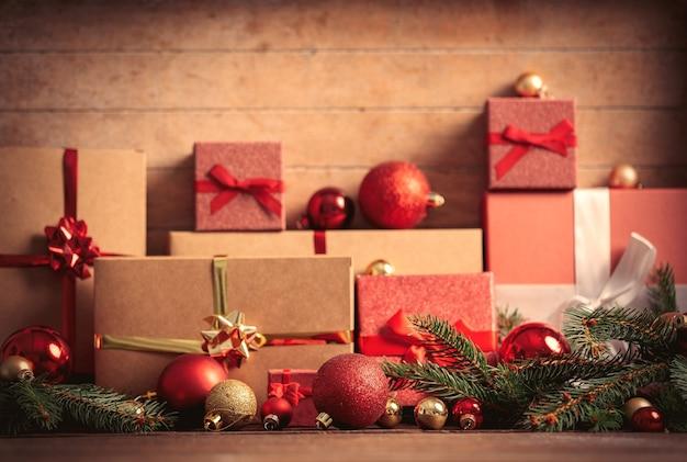 Рождественские подарки и безделушки с сосновой веткой на деревянном столе