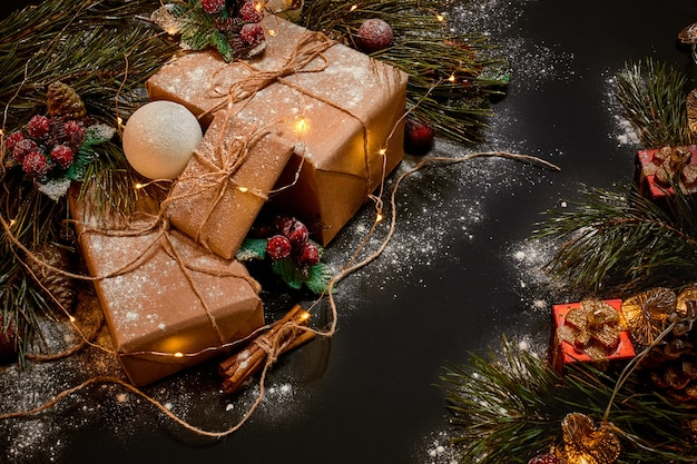 黒の背景に緑のトウヒの枝の近くにクリスマスプレゼントと花輪。クリスマスの背景。上面図。スペースをコピーします。静物。フラットレイ。新年