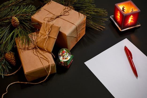 Рождественские подарки и ноутбук, лежащий рядом с зеленой еловой веткой на черном фоне, вид сверху. скопируйте пространство. натюрморт. плоская планировка. новый год