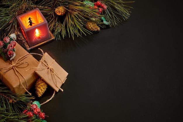 クリスマスプレゼントと黒の背景に緑のトウヒの枝の近くに赤いローソク足。クリスマスの背景。上面図。スペースをコピーします。静物。フラットレイ。新年