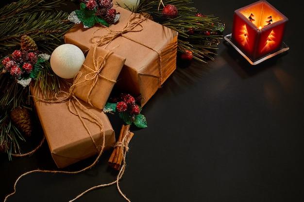 Рождественские подарки и красный подсвечник возле зеленой еловой ветки на черном фоне. рождественский фон. вид сверху. скопируйте пространство. натюрморт. плоская планировка. новый год