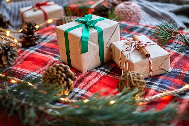 Christmas gifts on the background of a red woolen checkered plaid with garlands of cones and fir branches