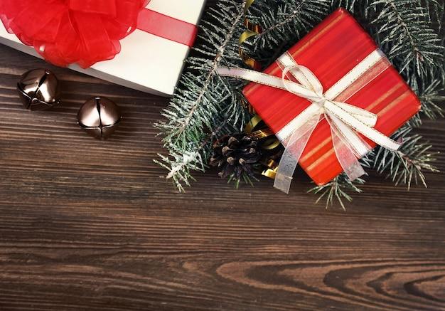 木の板に枝と鐘とクリスマスプレゼントの背景