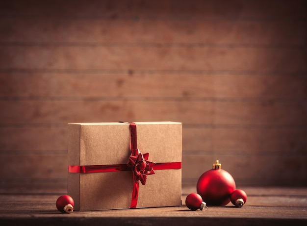 Christmas gifts and baubles on wooden table and background
