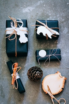 Christmas gifts in black packing with tags, confetti and wooden decor on a gray background