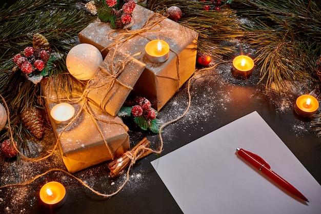 クリスマスプレゼント、燃えるろうそく、黒の背景の上面図の緑のトウヒの枝の近くに横たわっているノートブック。スペースをコピーします。静物。フラットレイ。新年