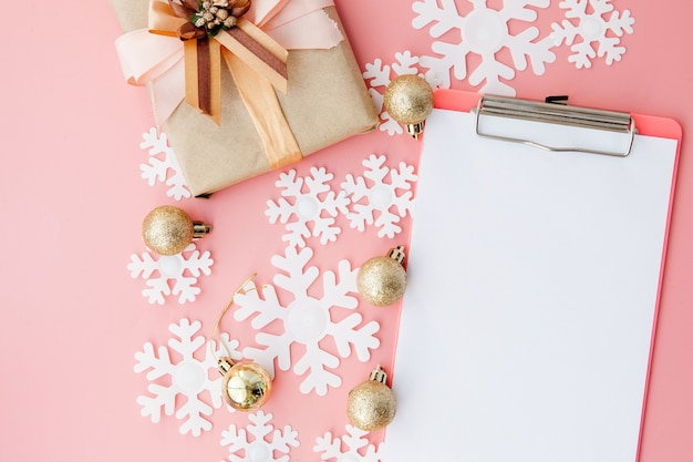 Christmas gifts, christmas ornaments and an open blank notebook on pink background