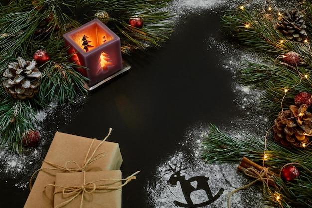 Рождественские подарки, елка, свечи, цветной декор, звезды, шары на черном фоне. вид сверху. скопируйте пространство. натюрморт flat lay новый год