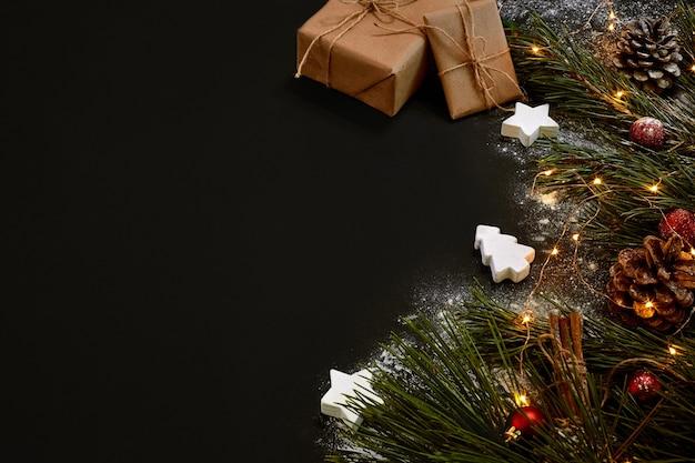 Рождественские подарки, елка, цветной декор, звезды, шары на черном фоне. вид сверху. скопируйте пространство. натюрморт. заложить квартиру новый год