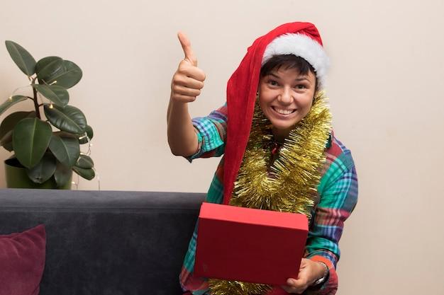 크리스마스 선물 개념 : 오픈 선물 상자와 산타 모자를 쓰고 행복 한 젊은 여자