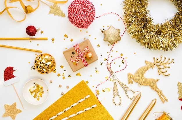 Christmas gifts and decorations in gold colors flat lay on a white background