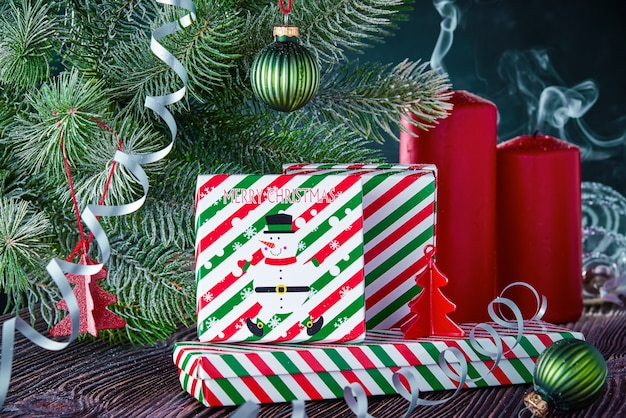 Christmas gifts, extinguished candles and decorated with a spruce branch. new year's background with free space for text.