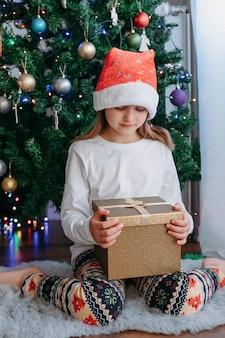 Рождественские подарки для детей. милая кавказская девушка в новогодней шапке открывает коробку с подарком под новогодней елкой. вертикальная ориентация.
