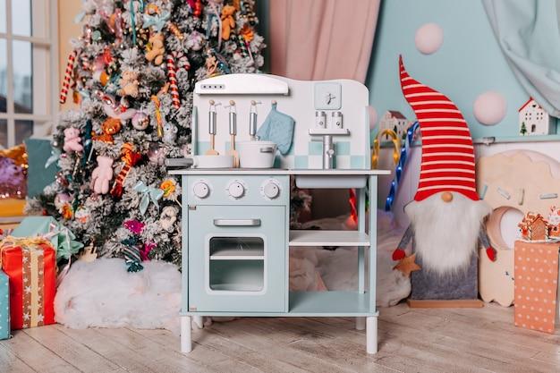 나무 아래에서 아이들을위한 크리스마스 선물. 소녀를위한 장난감 부엌 선물. 크리스마스 트리 아래 선물입니다. 장난감 나무 주방과 요리.