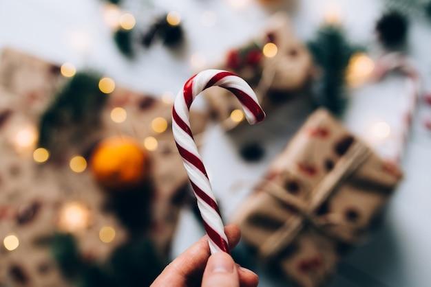 クリスマスプレゼント、手は白い木製のテーブルにロリポップ、タンジェリンを保持します。