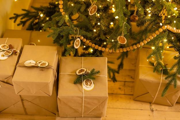 黄色、ピンク、白のリボン、松の枝、花輪が付いたクラフト紙のクリスマスプレゼント