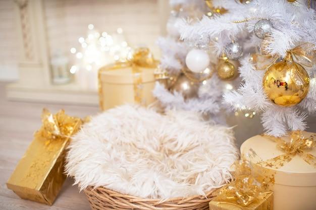 Рождественские подарки в большом количестве лежат под белой елкой, украшенной золотыми шарами. цилиндрическая шкатулка, украшенная лентами и золотой лентой. новый год уютный фон