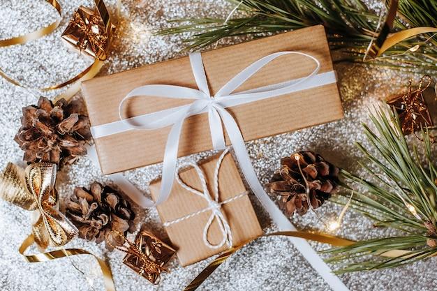 은색 배경에 축제 새해 분위기에서 소나무 콘과 전나무 가지와 조명 크리스마스 선물