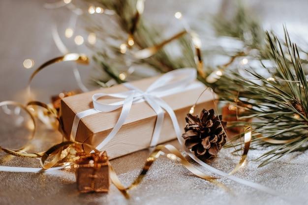 Рождественские подарки в огнях с шишками и еловыми ветками в праздничной новогодней атмосфере