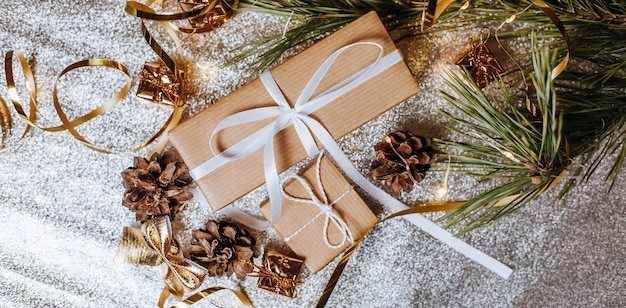 Рождественские подарки в огнях с шишками и еловыми ветками