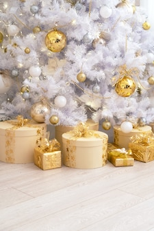 Christmas gifts in large numbers lie under a white tree decorated with golden balls. cylinder box decorated with ribbons and gold ribbon. new year cozy background