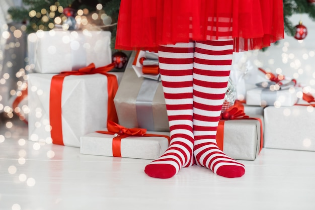 Christmas gifts and legs in stripe tights.