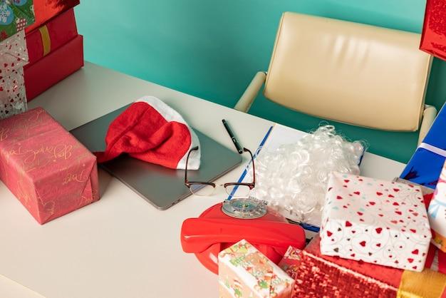 現代のサンタのオフィスのテーブルにクリスマスプレゼントがあります